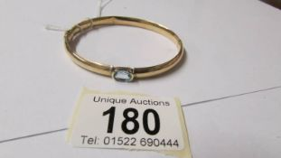 A 9ct gold and aquamarine bangle, 10 grams (some dints on inside).