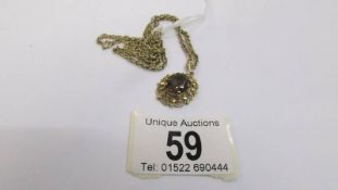 A fancy gold work pendant set with 9 smoky quartz in oval mount with attached 9ct gold chain,