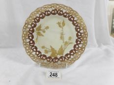 A gilded plate with fretwork rim decorated with brambles, marked CT on base.