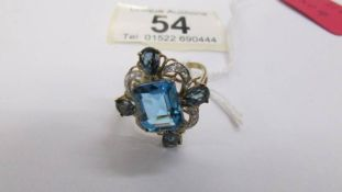A very unusual design blue topaz and diamond ring in 9ct gold.