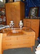 A 1960's bedroom suite comprising wardrobe, dressing table and chest of drawers.