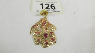 A stone set floral design pendant (tests as 24ct gold).