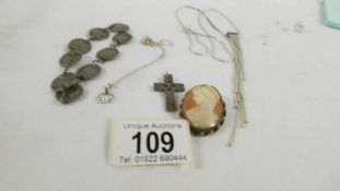 A silver necklace, a silver pendant on chain, a silver cross,