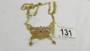 A necklace on long chain, (tests as 24ct gold) 30 grams.