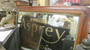 An overmantel mirror with Asprey signage.