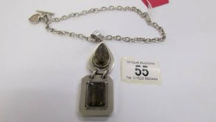A quality smoky quartz heavy silver pendant and chain with attached heart charm.