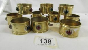 A set of 10 arts and crafts brass napkin rings with multi coloured bead insets.