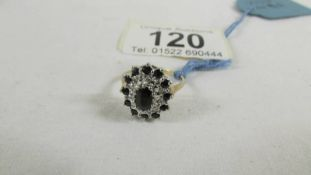 A diamond and sapphire cluster ring in an oval design, size K.