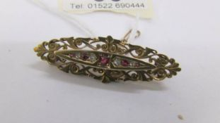 An antique ruby and diamond brooch in 15 carat hall marked gold with attached safety chain.
