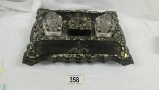 A Victorian papier mache' and mother of pearl desk stand.