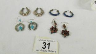 4 pairs of silver earrings.