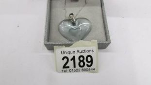 A Lalique heart shaped glass pendant on chain.