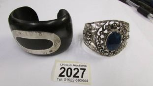 An ebony vintage wood bangle set with a silver oval to top together with a stone set intricate lacy