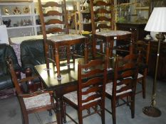 A dark oak draw leaf table with 8 matching ladder back chairs.