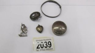 A silver bangle, a silver brooch, a silver badge, a silver locket and a silver pill box.