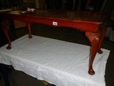 A dark wood stained long coffee table.