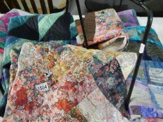 A collection of patchwork quilted squares and a cushion cover