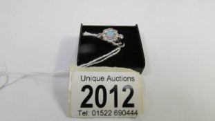 An 18ct gold ring set central opal surrounded by diamonds, size M.
