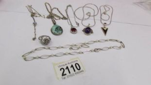A mixed lot of pendants etc., including some silver.