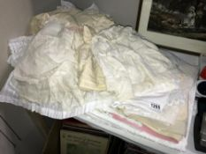 A quantity of misc. linen, includes table clothes, material, net curtain, vintage baby clothes etc.