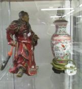 A Chinese figure and a Chinese lamp base.