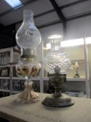 A silver plated candle lamp and a gilded glass oil lamp