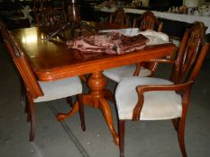 A dark wood stained extending dining table with 2 leaves and 6 chairs.