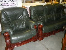 A green leather 3 seat sofa and chair with dark wood frames.