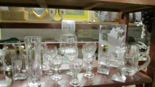 A shelf of glass ware including scent bottles.