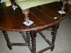 A Victorian oak gate leg table on barley twist legs.