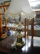 A brass effect table lamp with shade