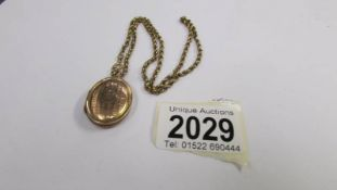 A rose gold 9ct back and front locket, engine turned on a 9ct gold chain, total weight 10.9 grams.