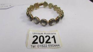 A 14 carat gold 15 stone bracelet set large diamonds surrounded by small diamonds.