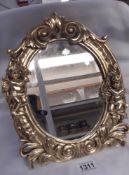 A decorative gilt framed oval mirror