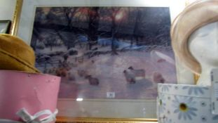 A large framed and glazed winter scene print with sheep.