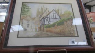 A framed and glazed village scene signed Janet Nichols '98.
