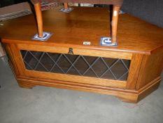 A darkwood stained corner unit with leaded glass panel