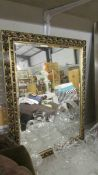 A gilt framed bevel edged mirror.