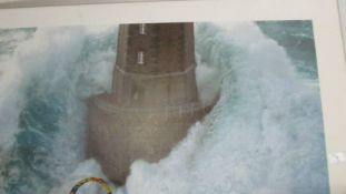 A large framed and glazed print of a lighthouse in rough seas.