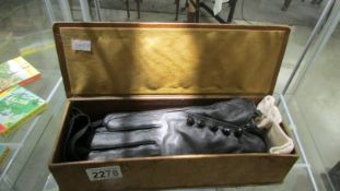 An old glove box and 3 pairs of vintage gloves.