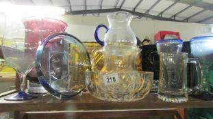 A shelf of assorted glass ware.