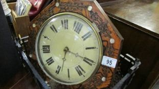 A wall clock with brass weights.