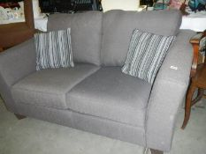 A grey fabric 2 seater sofa with 2 matching cushions