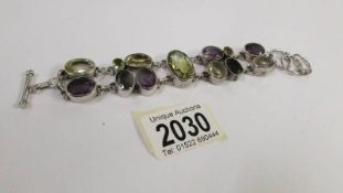 An amethyst and citrine set bracelet in a heavy silver mount.