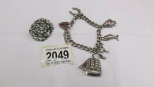 A vintage silver charm bracelet dated Birmingham 1976 together with a white stone brooch circa