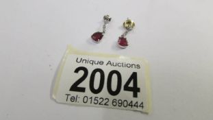 A pair of 14ct white gold and ruby earrings.