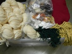 A box of tapestry threads, fringing and textile pieces.