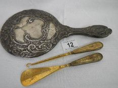 A silver hand mirror in good condition together with a silver handled button hook and a silver