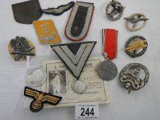 A quantity of replica German cloth and other cap badges etc.
