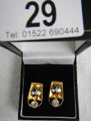 A pair of diamond and enamel earrings, test as 22 ct gold, in good condition.